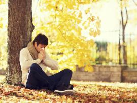 man sitting under a tree with yellow fall leaves blowing his nose