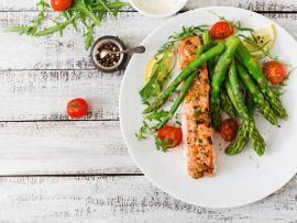 salmon on a plate with tomatoes and asparagus