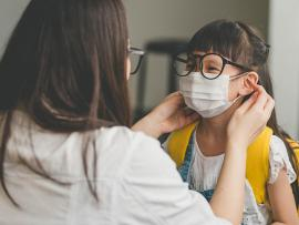 mom putting mask on daughter wearing glasses before school
