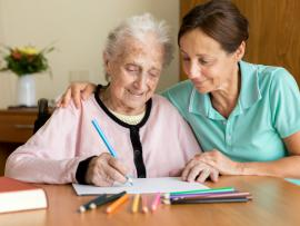 daughter helping her mother deal with dementia by doing some art