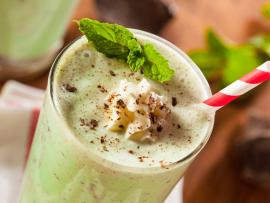 A healthy minty smoothie garnished with chocolate and a red-and-white striped straw.