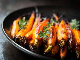 Oven-roasted whole carrots with thyme, in a black plate on a slate tabletop.