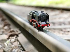 toy steam train model in focus perched on real train track with blurred background