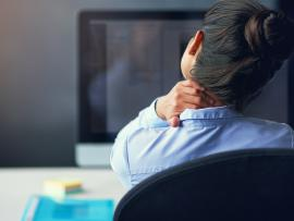 professional woman rubbing a stiff neck after hunching over computer at work all day