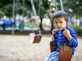 a young boy sitting alone on a playground