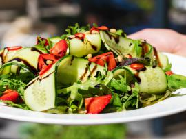 plate of salad with strawberries, cucumbers and balsamic dressing