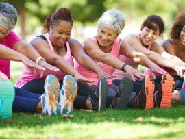 a diverse group of women stretching in the park before a workout