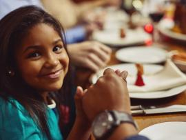 closeup of young girl's smiling face with holiday table in background