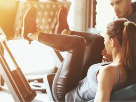 trainer at gym helping woman do knee exercises