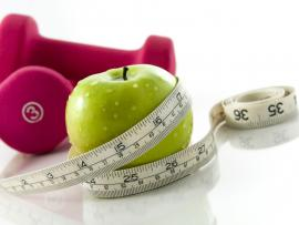 green apple, measuring tape and hand weights