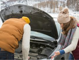 two people on the side of a road in winter trying to fix a car