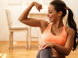 happy athletic woman flexing her bicep