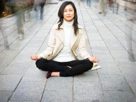woman sitting in a zen position in the middle of people walking