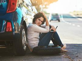 woman holding lug wrench sitting by car with flat tire