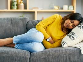 woman with severe cramps laying on couch