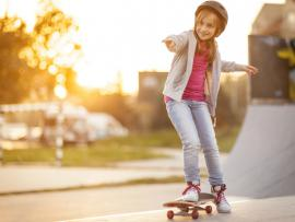 young girl riding a skate board with a helmet on.