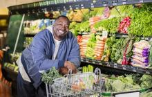 smiling overweight man leaning on grocery cart filled with fresh produce