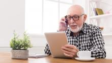 bald senior man with glasses using smartphone and tablet