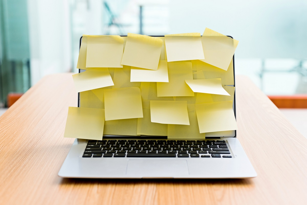 laptop covered in yellow sticky notes